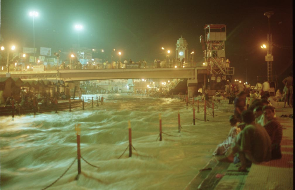 A night photograph of the raging river ganges. The street lights bathe the scene in an incandescent glow while the cloudy depths of the river seem hard as stone.