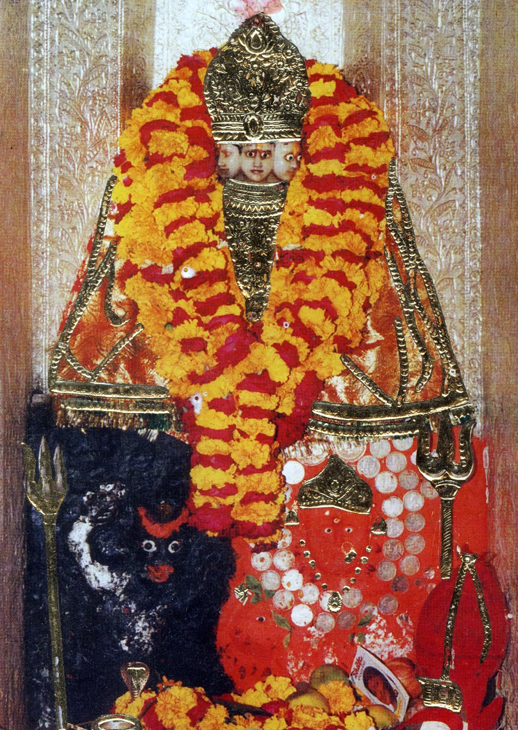 A stone statue heavily bedecked in bright flower garlands and gold plated jewlery
