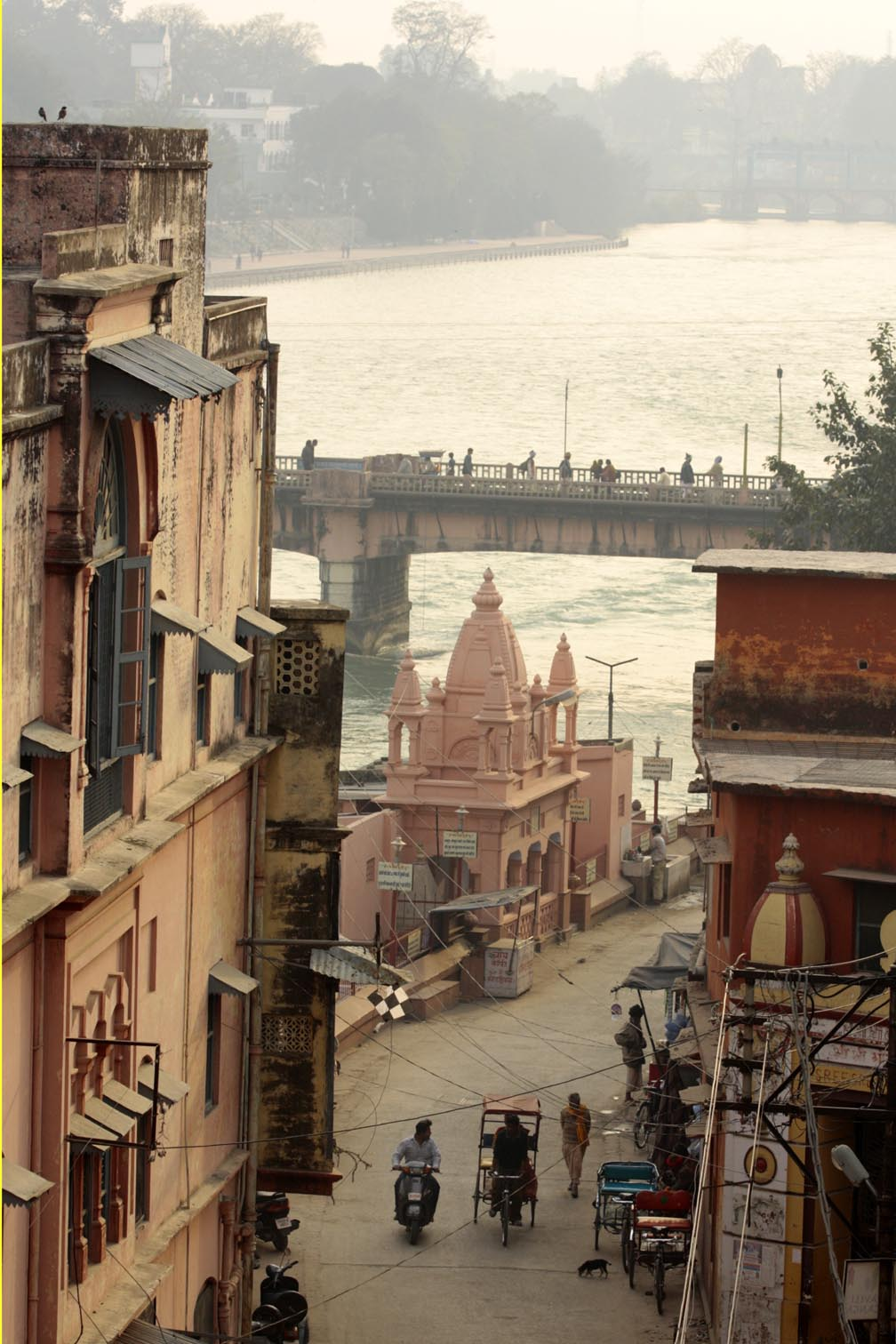 Buildings line a cobblestone street. The bridge that crosses the ganges is in the distance with the river continuing into the distance.