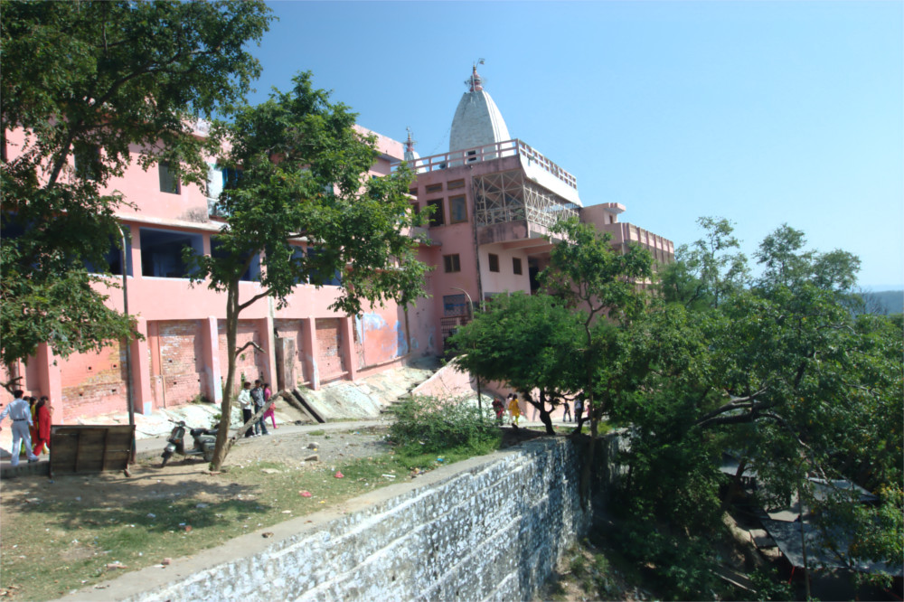 The pink temple building is beatifully framed by the bright blue sky. The building sits on a large earth carved terrace with a tree in the foreground.