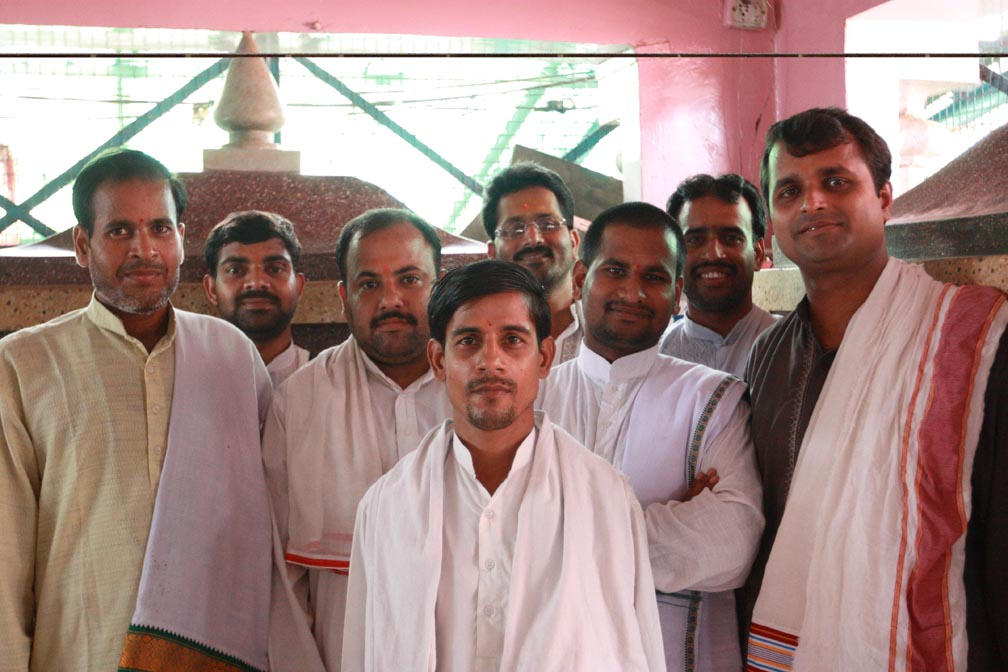 A group of men dressed in kortas and dhotis smile at the camera. They are the pandits and have just taken part in the latest yagya.