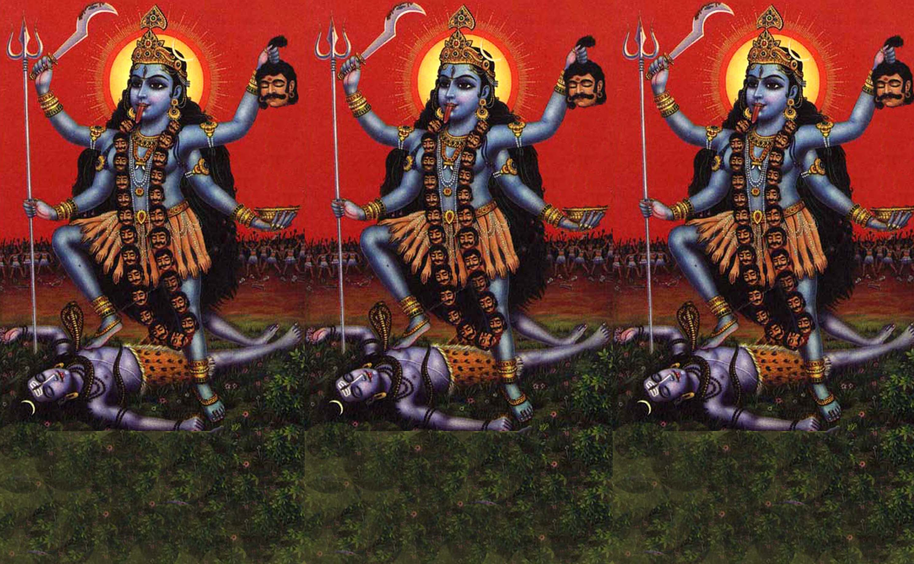 Kali is depicted here with blue skin and a garland of severed heads. She holds a khopesh (saber) and a severed head. Her tongue is obscenely long to catch the blood that drains from the heads. She stands on the body of a sleeping shiva.